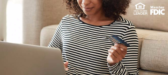 WOMAN HOLDING HER CREDIT CARD AND WORKING ON A COMPUTER